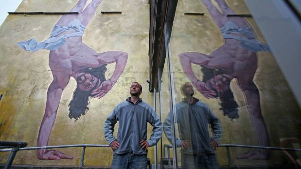 Artist Cosmo Sarson sits besides a giant mural of Jesus breakdancing that he has painted on the 8.5 metre wall beside ...
