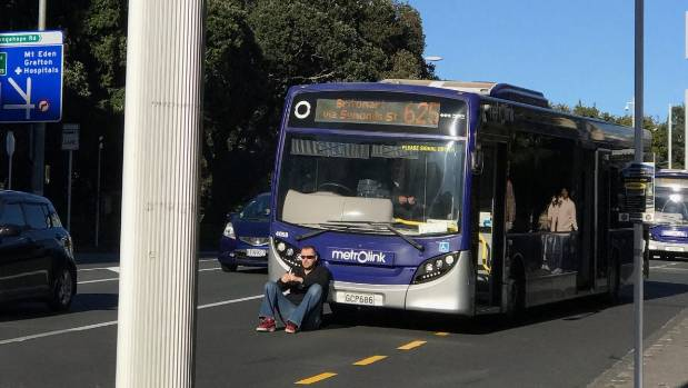 The man sat on a road in front of a bus after the driver refused to open the door.
