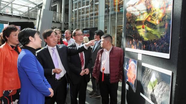Chinese consul general to Christchurch Zhijian Jin points out a photo to deputy mayor of Enshi, Xianhong Zhang (in blue).