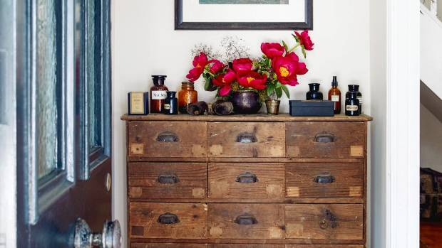 Vintage apothecary bottles sit on the antique sideboard – a birthday gift for Amanda from Andrew that looks as if it had ...