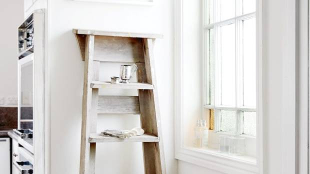 A vintage ladder doubles as a shelf in the kitchen.