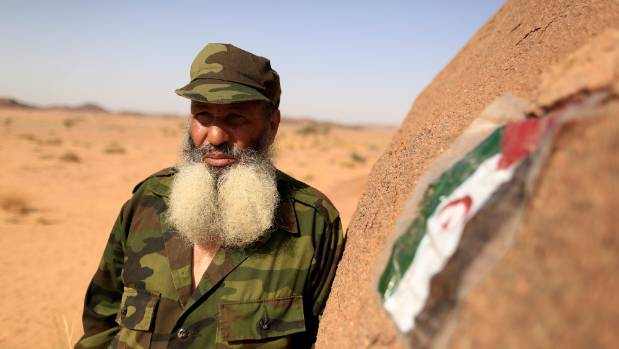 Mohamed al Wali, 65, a Polisario fighter, stands next to a Sahrawi Arab Democratic Republic flag at a forward base on ...