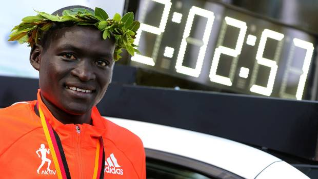 Dennis Kimetto poses by the race clock with his world record marathon time