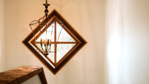 A diamond-shaped stairwell window offers a peek at the woodland garden.