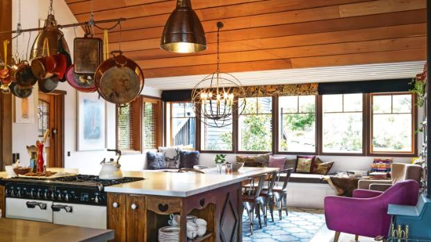 Beyond the kitchen, generous window seating invites the cook to abandon the stove and read instead; rugs scattered over ...