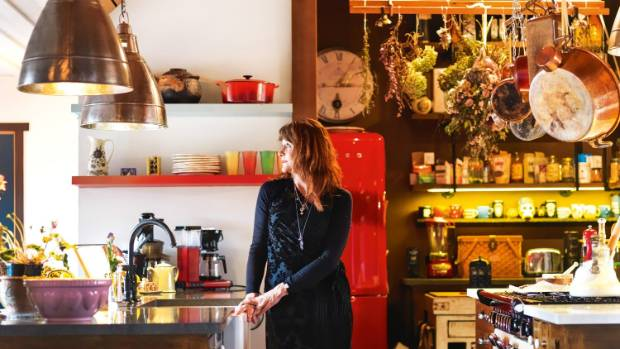 Catherine in the kitchen; produce and pots are suspended in the open pantry.