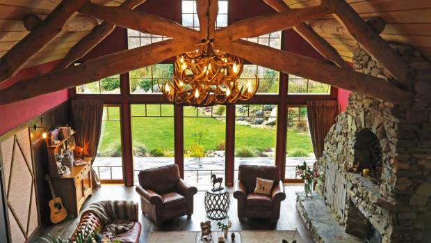 A view of the great room in Tim and Catherine Davis' Wanaka home, with herb garden, lake and alpine views beyond; the ...