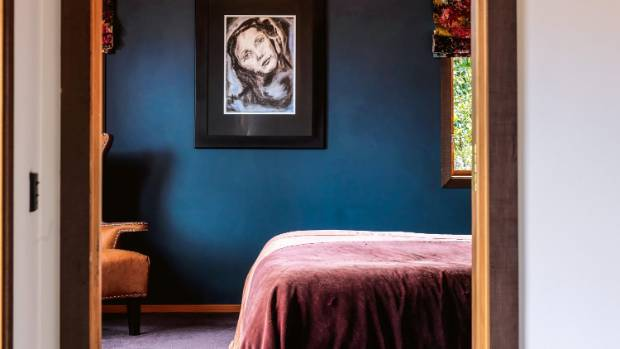 In the master bedroom, a deep steel blue is enlivened with abstract florals; the artwork by Catherine is a graphite and ...