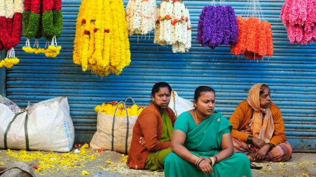 Vendors selling flower garlands on a pavement wait for customers outside a flower market in the southern Indian city of ...