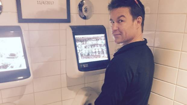 Co-owner Jonny Kirkpatrick gives the interactive digital urinal a go at Dux Central in Christchurch.