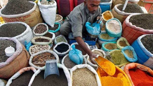 A vendor sells spices on a street at a market in India.