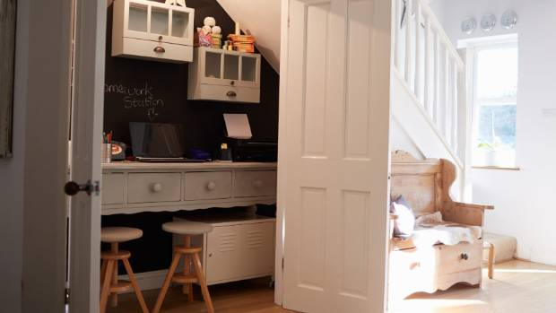 Wasted space under the stairs is converted into a home office, and the doors can be closed to hide the mess.