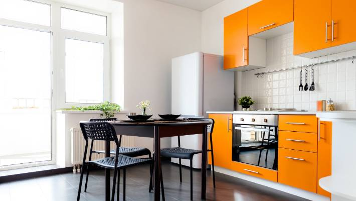 Bright Orange Painted Cabinets And Drawers Certainly Brighten Up A White Kitchen