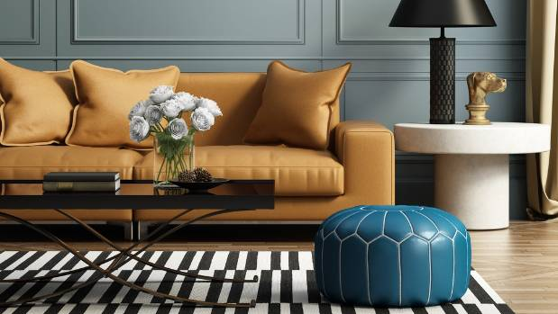 The eye catching blue ottoman adds drama to this living space.