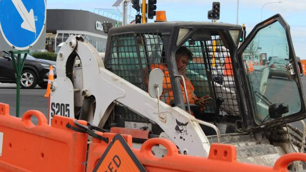 A worker at the corner of  Edmonton Rd and Te Atatu Rd in Auckland. AT has said they could have worked on better ...