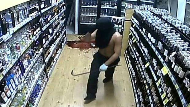 A smashed wine bottle covers the floor as a crowbar-wielding robber stalks the Liquorland store.