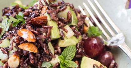 Black rice salad with avocado, grapes and almonds.