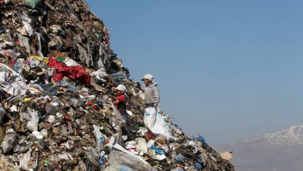 Boys sift through garbage at a dump near a makeshift settlement for Syrian refugees in Lebanon. Years of living ...