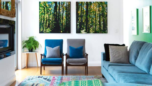 Bright jewel tones repeated in furniture, rugs and art help pull this room together visually.