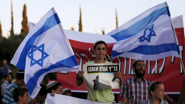 An Israeli protester holds a placard and a flag during a demonstration against a court decision to demolish housing ...