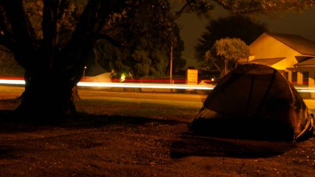 Cars zoom past Sheree Galatau as she sleeps in her tent on State Highway 2.