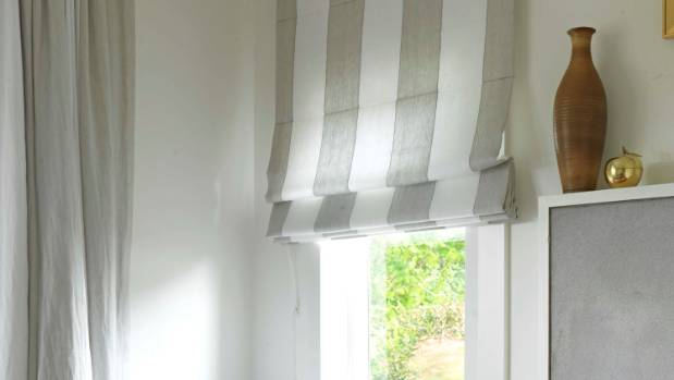 This room successfully mixes curtains and a Roman blind in a wide-striped fabric.