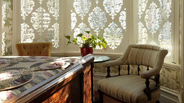 Wellington designer Debra DeLorenzo used filigree screens to provide privacy for this traditionally styled bedroom.
