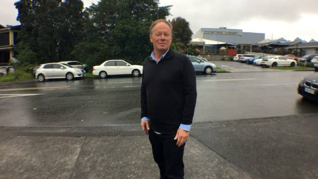 Trethewey stands in front of his childcare centre, right, and the site for the new building, where the trees are to the left.