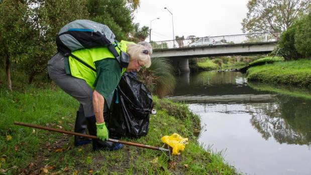 Kris Wilson picks up rubbish along the Heathcote River during the Mother of All Clean Ups event on Saturday.