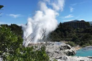 Pohutu geyser erupts, sending showers of boiling water into the air over 'The Blueys'.