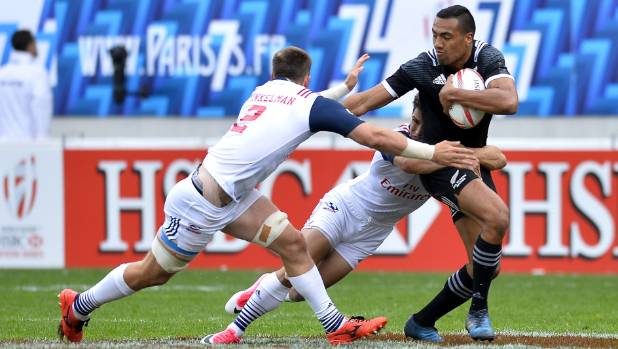New Zealand's Sione Molia fends off defenders from the USA during pool play in Paris.