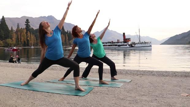 Amanda, Sandi and Debbie practice yoga on the shore of Lake Wakatipu.