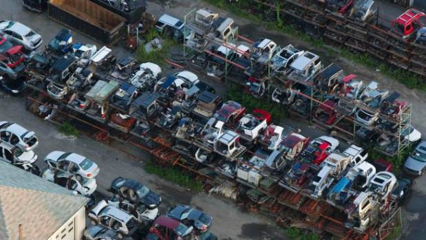 Cars and car parts stand stacked at a wrecking yard in the US. A new report predicts the whole of land transport will ...