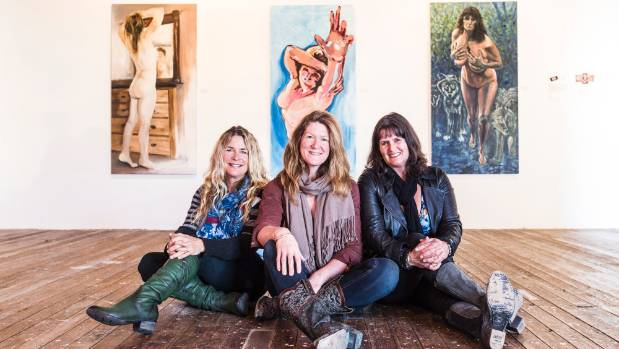 Lisa DeVries, Kirstie Hogg, and Jane Duncan with self-portraits from Us, at the Refinery ArtSpace.