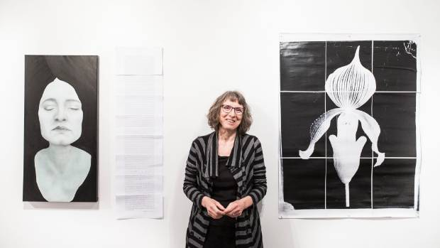Curator Catharine Salmon with work from TLC at the Refinery ArtSpace.
