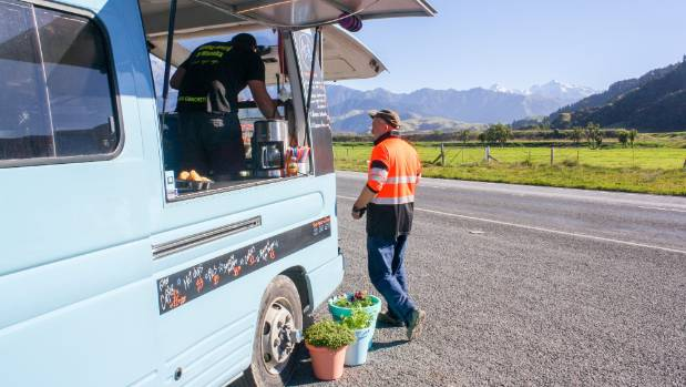A road worker grabs a pie and filter coffee from the Azul Food Truck on State Highway 1, Clarence.