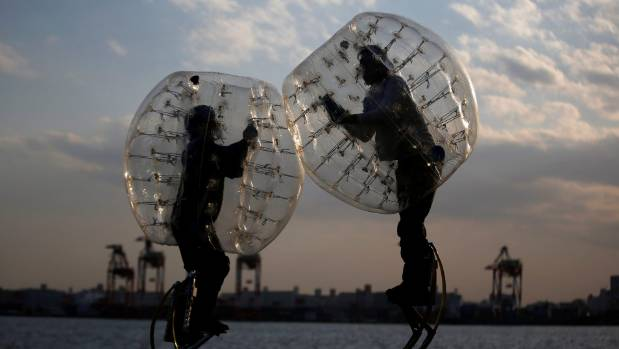 "Ryoichi Ando , 27, an inventor of ""Bubble Jumper"", competes with his opponent as they demonstrate the sport in Tokyo."