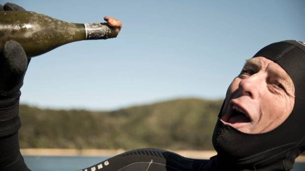 Martin Homes of Abel Tasman Sailing strikes a pose with an old bottle found on the sea floor during a  clean up by the ...