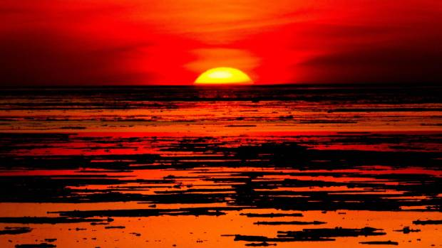 This photo was taken looking out onto Lake Huron, from Grand Bend in Ontario Canada, at sunset, as ice was starting to ...