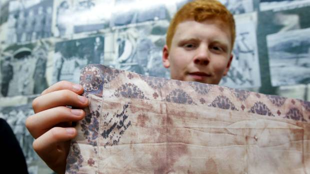 Stephen Potter, of Invercargill, holding the replica copy of the handkerchief belonging to their ancestor George Thomas ...