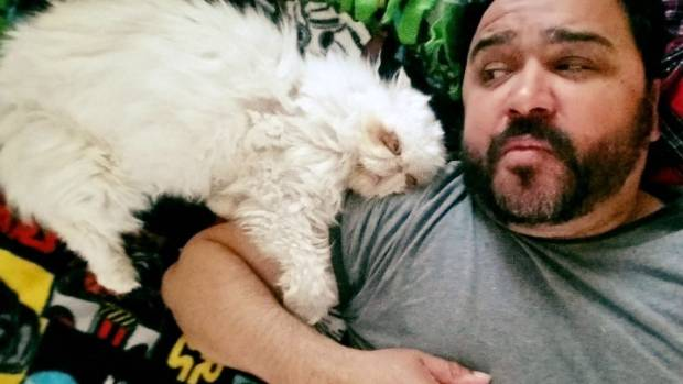 Sinbad cuddles with Elliott Serrano, the shelter employee and animal advocate who first fostered and then adopted him.