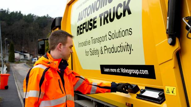 Truck operator/driver uses a control button on Volvo's autonomous driving rubbish truck.