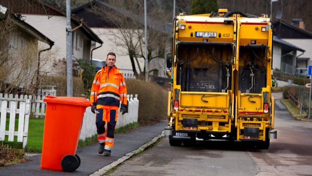 The operator/driver walks ahead of Volvo's reversing autonomous driving rubbish truck.
