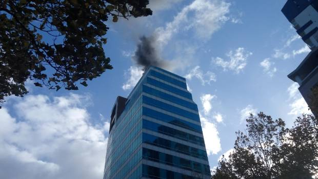 The fire is on the roof of the building.