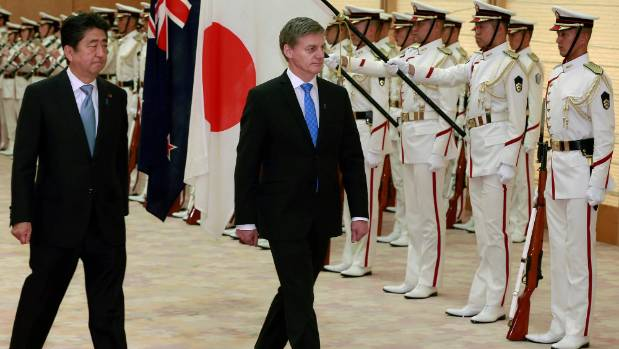 New Zealand Prime Minister Bill English accompanied by his Japanese counterpart Shinzo Abe reviews a guard of honor ...