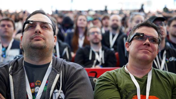 Two attendees wearing Google Glass listen to the opening keynote during the annual Google I/O developers conference.