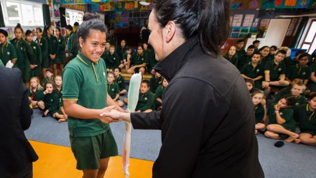 Sala Leitupo, 13, shakes Black Stick Kayla Whitelock's hand after receiving a hockey stick.
