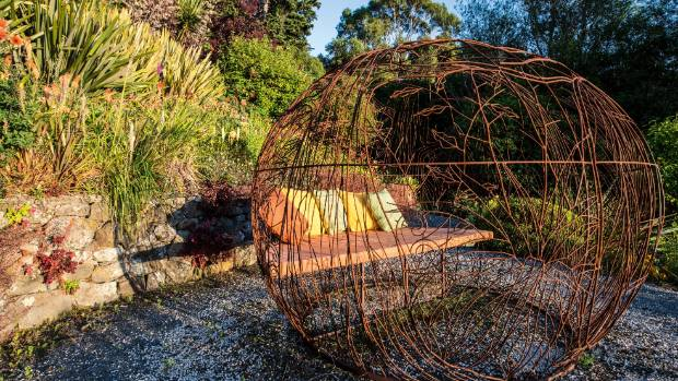 This rusty orb, sculpted by Sharon Earl of Hawarden, is a folly with a function, offering a snug sitting spot for ...