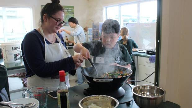 Aunty helper Ashley Davies supervises Daniel Guo as he cooks up a stir-fry using veggies grown in Forrest Hill School's ...