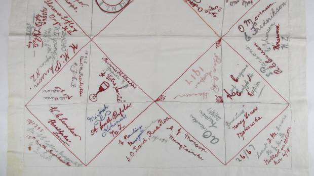 An embroidered white linen tablecloth held by Napier's MTG (Museum, Theatre, Gallery), features the names of some of the ...